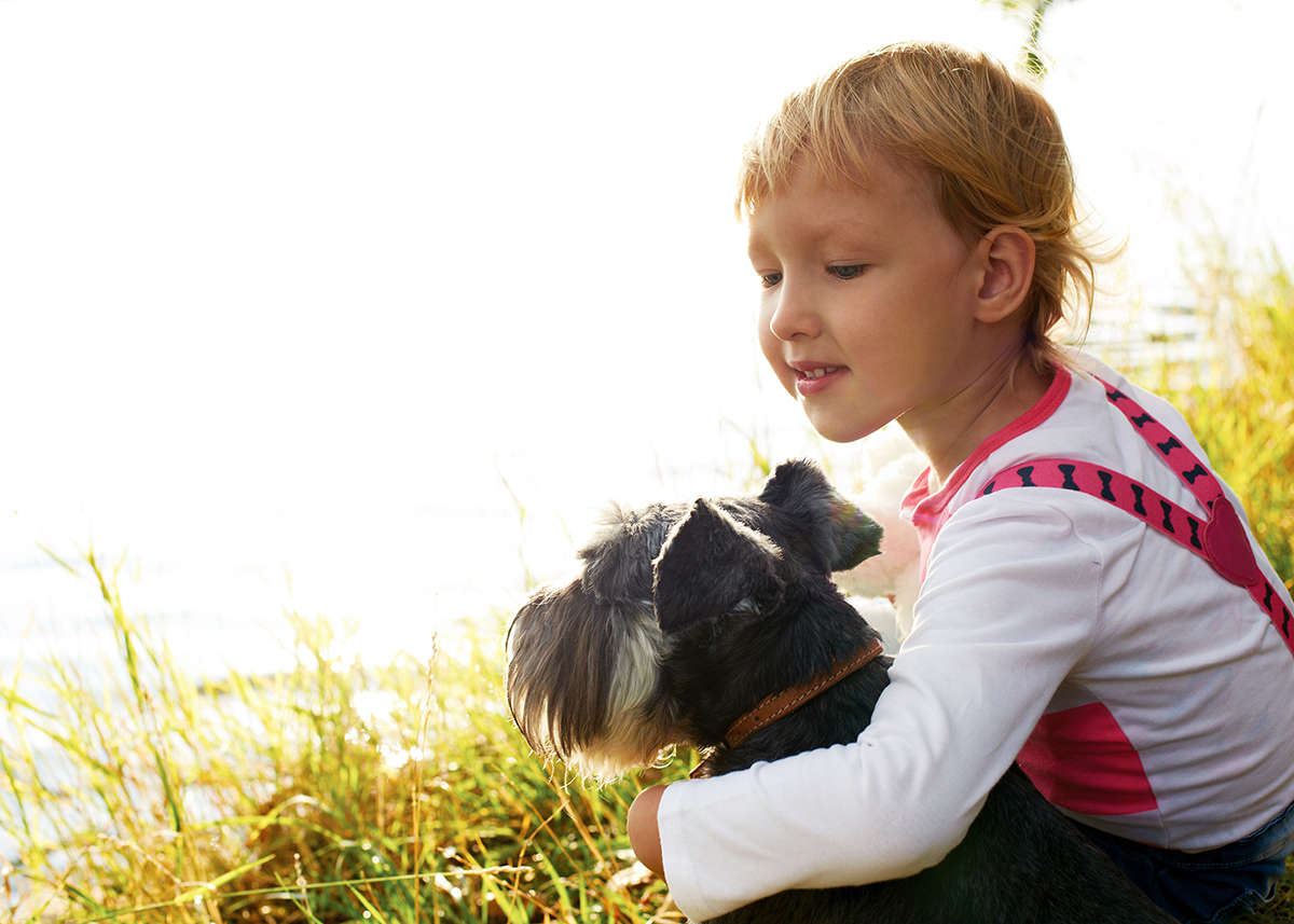 child with dog at lakes edge