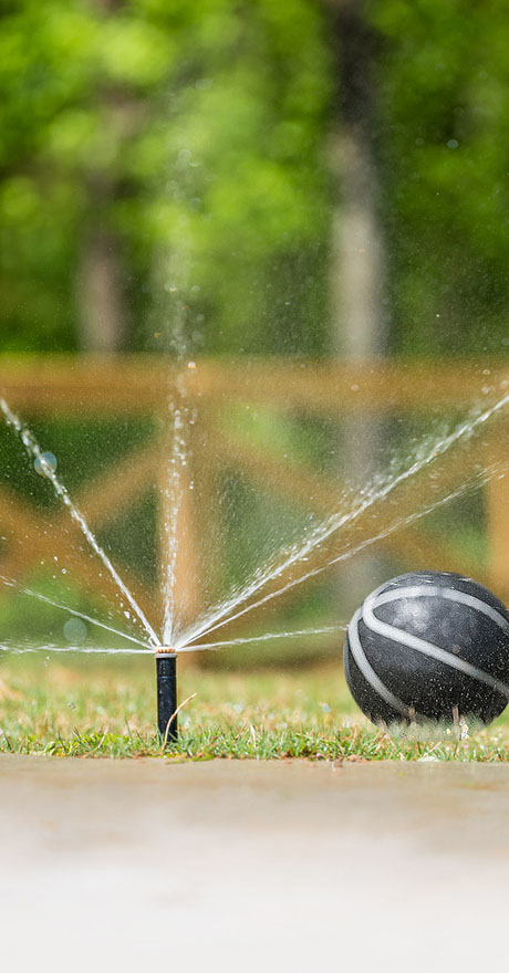 ball in yard of new home being watered with sprinkler Engle Park by Pratt Homes