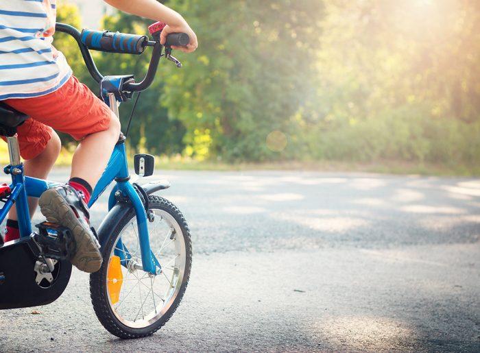 boy on bike riding down street in new community