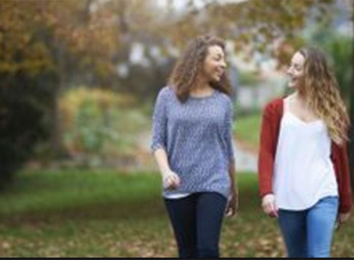 friends walking down wooded path in Pratt community